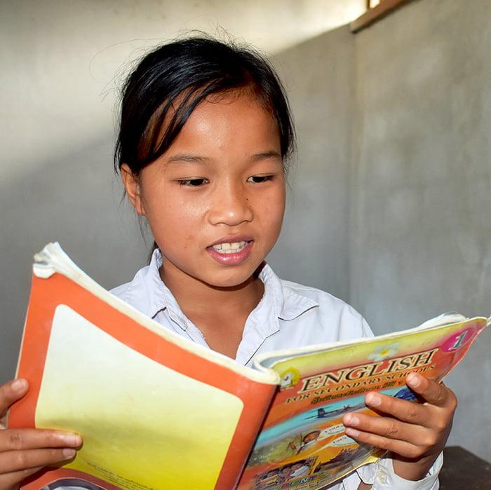 Laosilainen tyttö lukee oppikirjaa koululuokassa.
