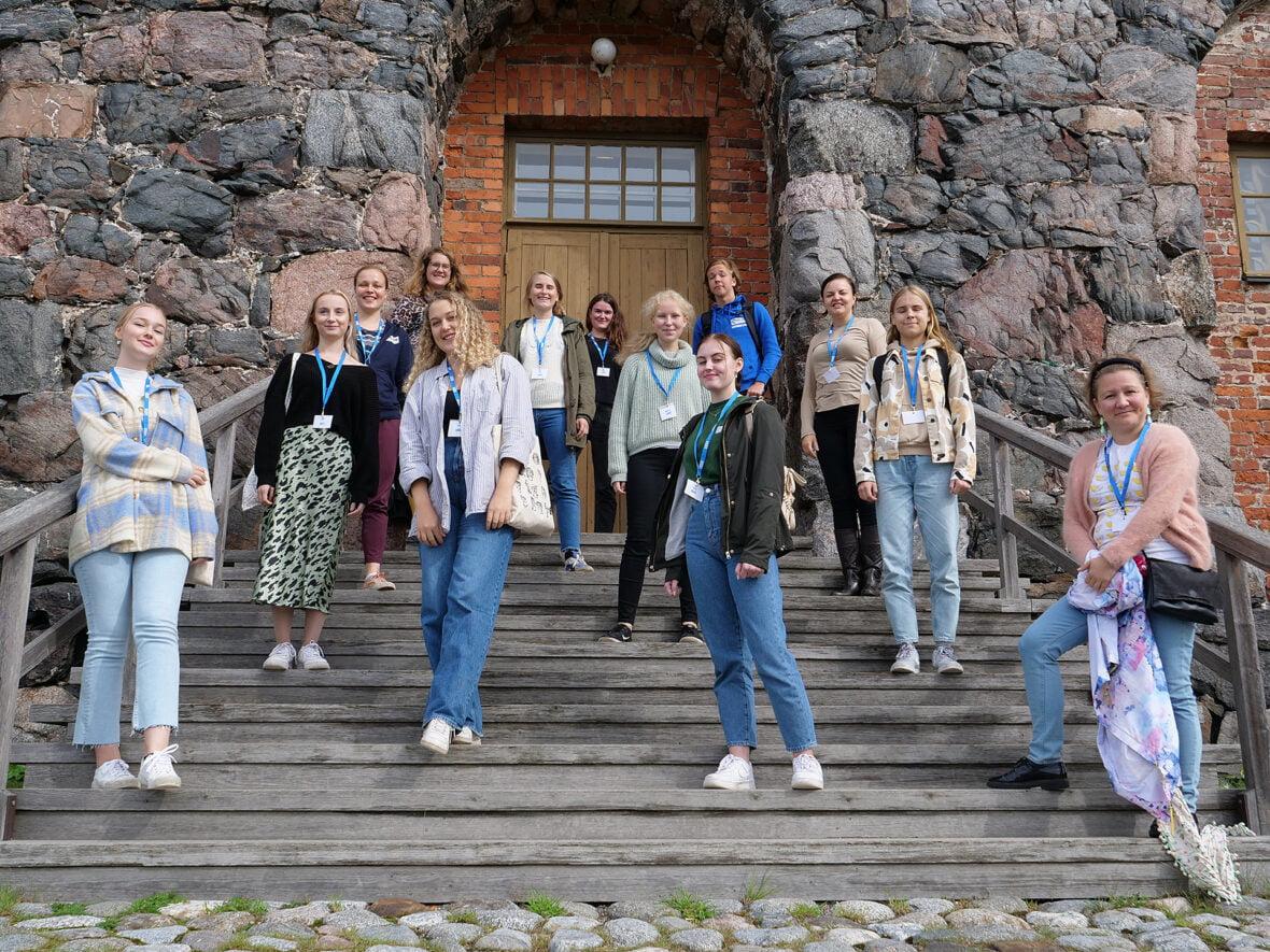Planin vapaaehtoisia ja työntekijöitä seisoo portailla siniset nauhat kaulassaan.