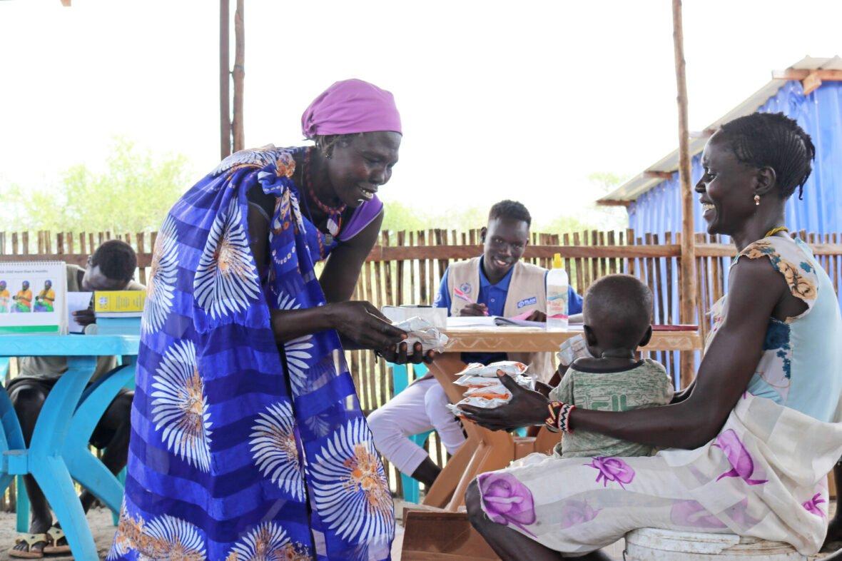 Planin paikallinen vapaaehtoinen antaa Etelä-Sudanissa ruokatarvikepaketteja hymyilevälle äidille, jolla on pieni lapsi sylissään.