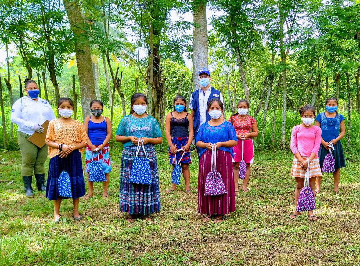 Planin työntekijöitä ja naisia maskit päällä metsän reunassa Guatemalassa.