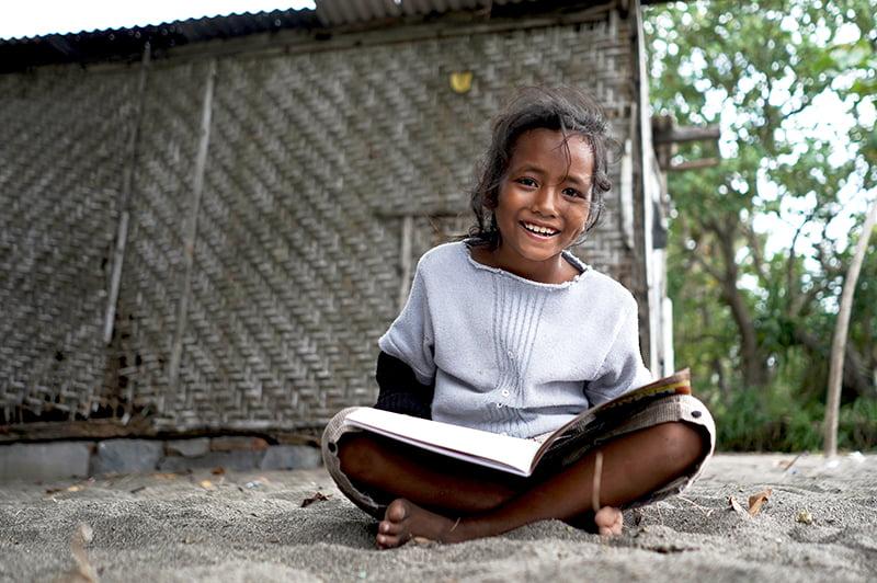Tyttö istuu hiekalla kirja sylissään ja hymyilee kameralle.