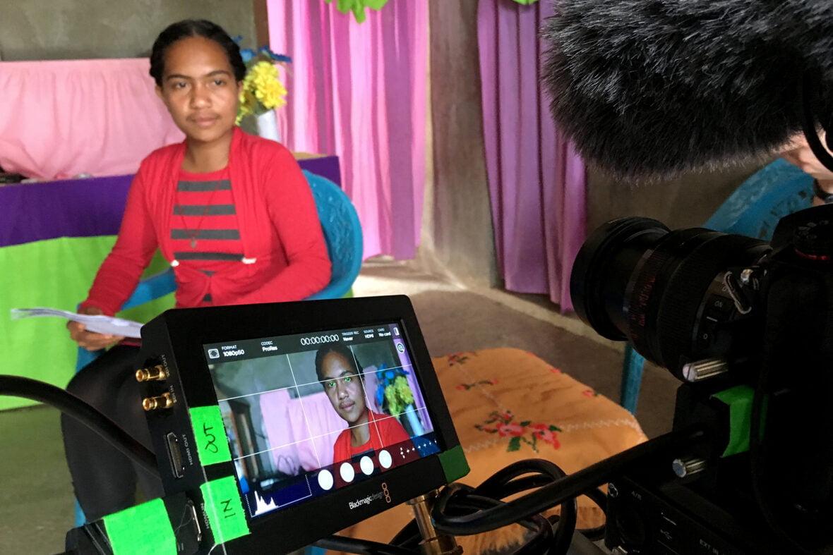 Itätimorilainen Francelina istuu ja puhuu videokameralle, jonka monitorista näkyy Francelinan kuva.