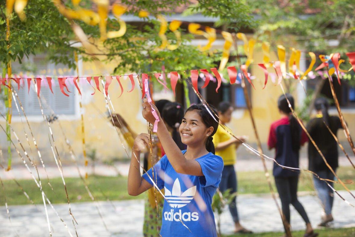 Kambozalainen tyttö ripustaa hymyillen koristeita juhlia varten.