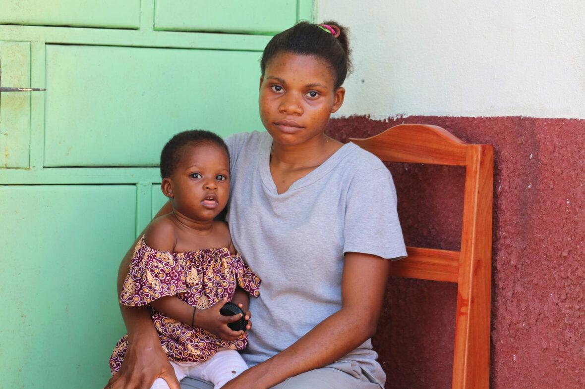 Kamerunilainen 19-vuotias Alice ja hänen kuusikuinen vauvansa istuvat vakavana tuolilla.