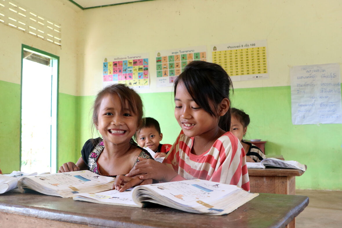 Kaksi pientä tyttöä istuu pulpetissa oppitunnilla ja hymyilee.