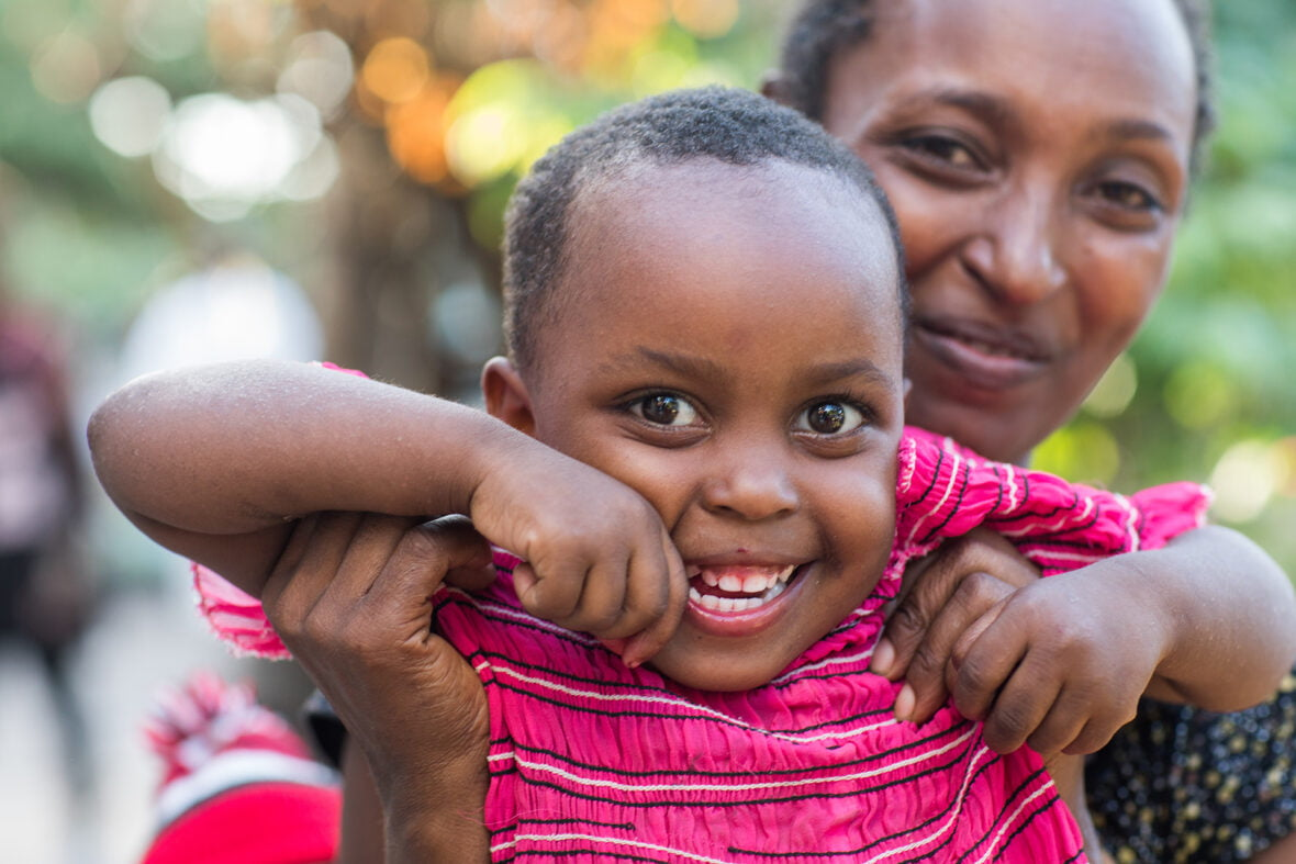 Tansanialainen lapsi hymyilee äitinsä sylissä.