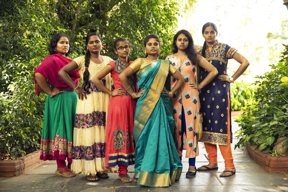 Kuusi intialaista tyttöä poseeraa vakavana kädet lanteilla.