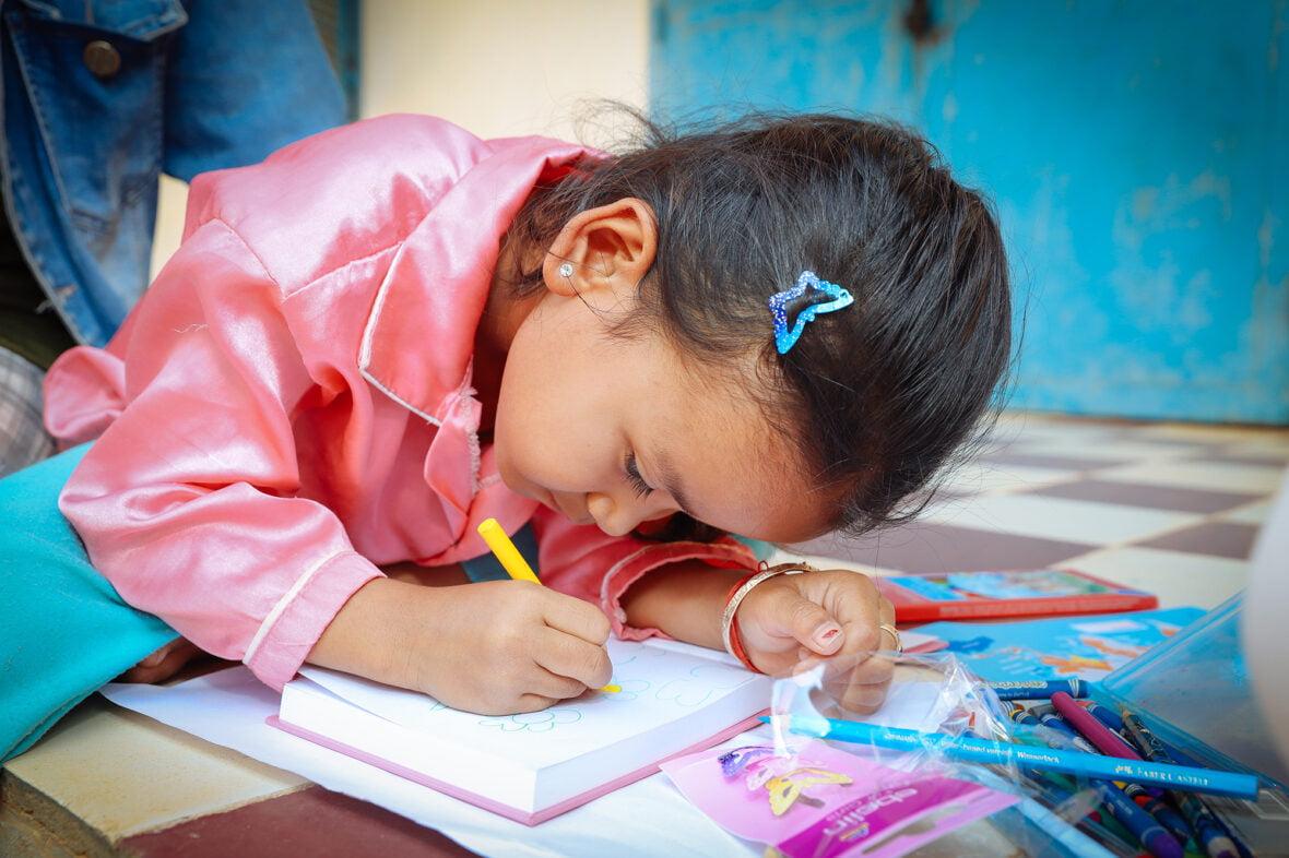 Pieni tyttö kirjoittaa keskittyneesti kirjaan Kambodzassa.