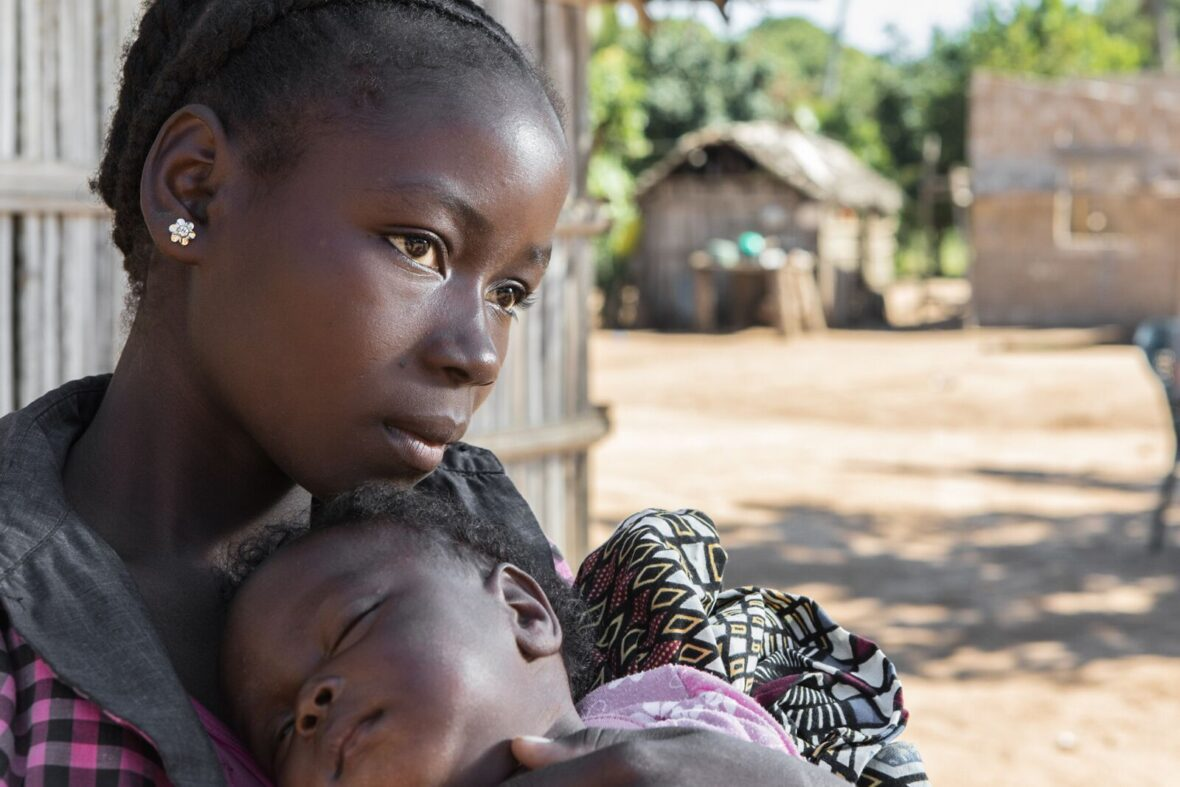 Pieni vauva nukkuu mosambikilaisäidin sylissä.