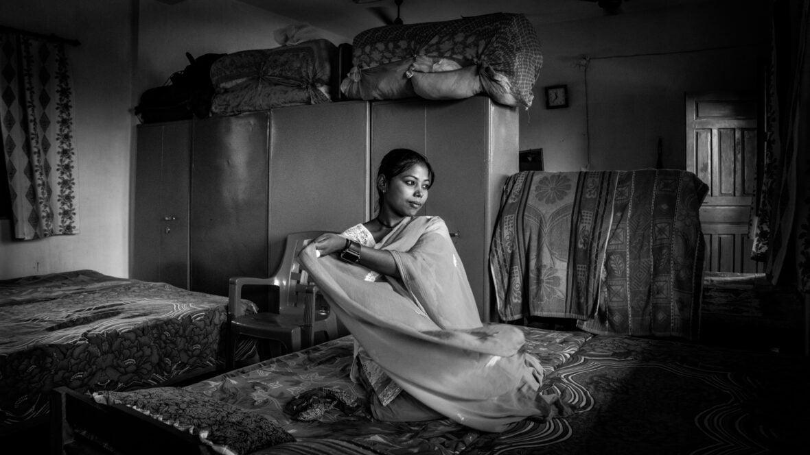 Nepalilainen tyttö istuu ja hymyilee ja heiluttaa huivia.