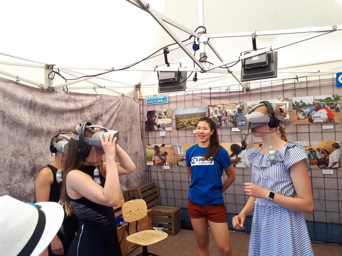 Planin vapaaehtoinen katselee, kun kaksi vierailijaa kokeilee virtuaalilaseja Planin osastolla SuomiAreena-tapahtumassa.