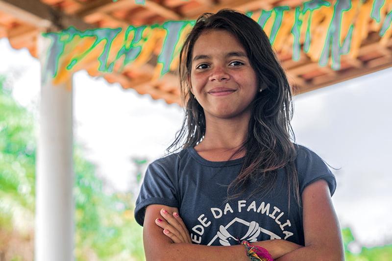Brasilialainen tyttö seisoo pihalla viirien alla.