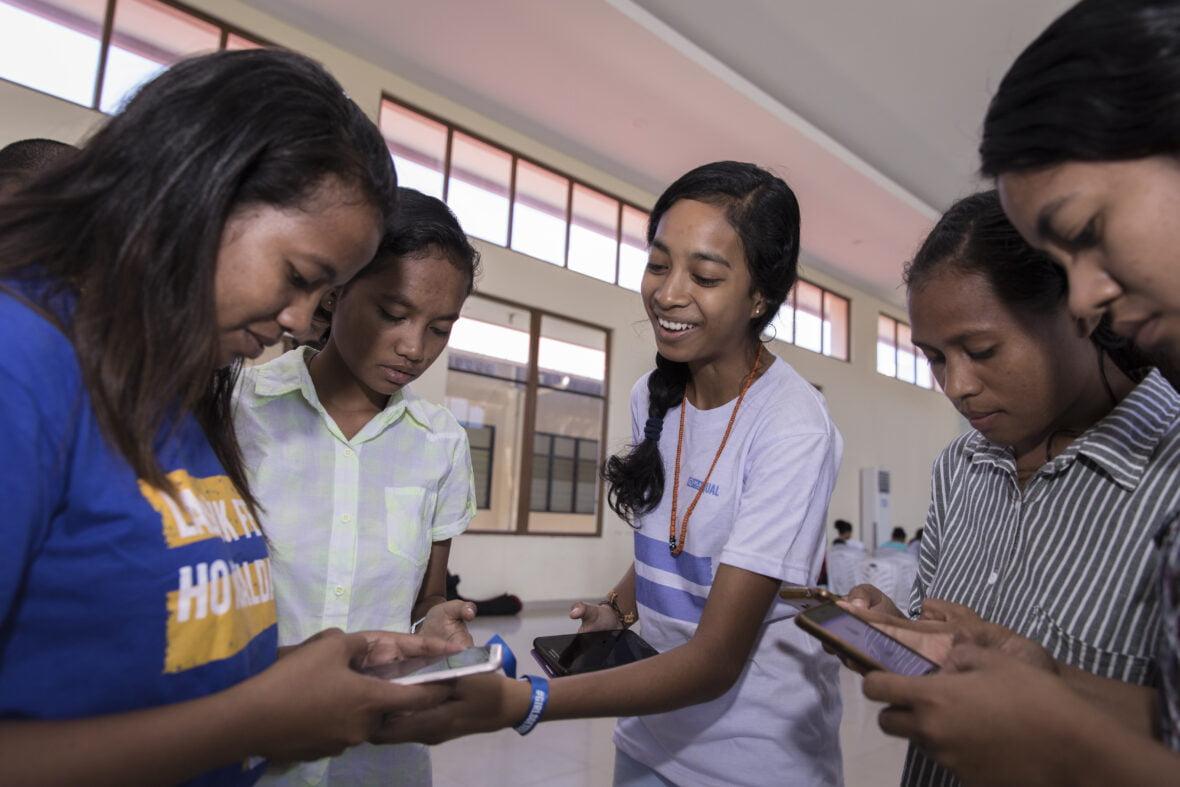 Itätimorilaisnuoret käyttävät yhdessä puhelimia ja nauravat iloisina.