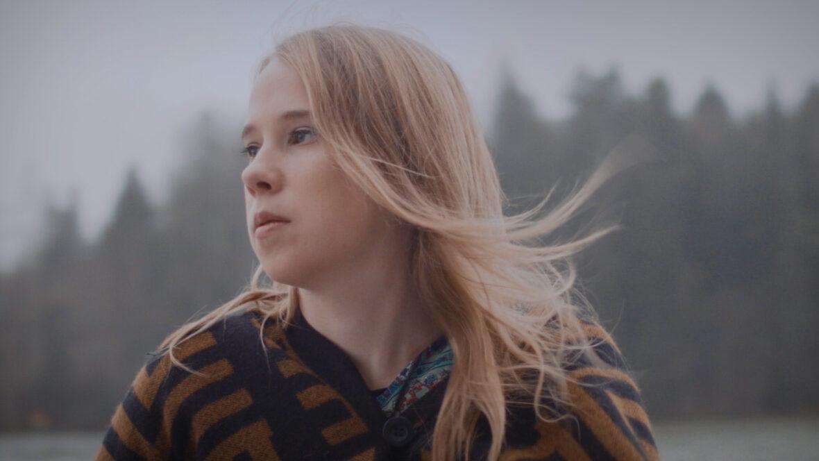 Vilma Talvitie katsoo vakavana sivulle, taustalla metsää.