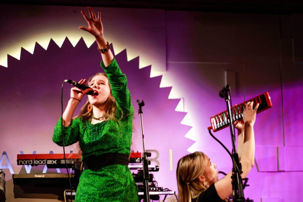 Vilma Talvitie laulaa lavalla, bändi taustalla.