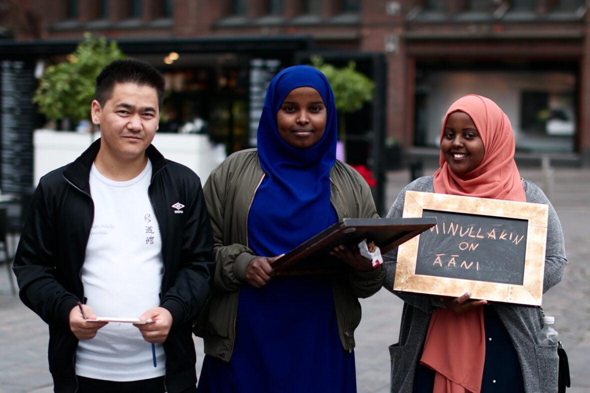 """Kolme henkilö kadulla. Yhdellä kädessä kyltti, jossa lukee """"Minulla on ääni."""""""