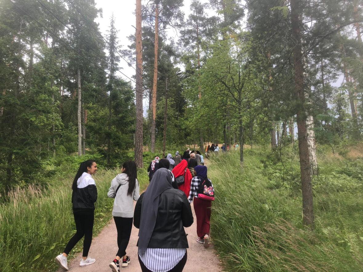 Joukko nuoria kävelee metsäpolkua pitkin.