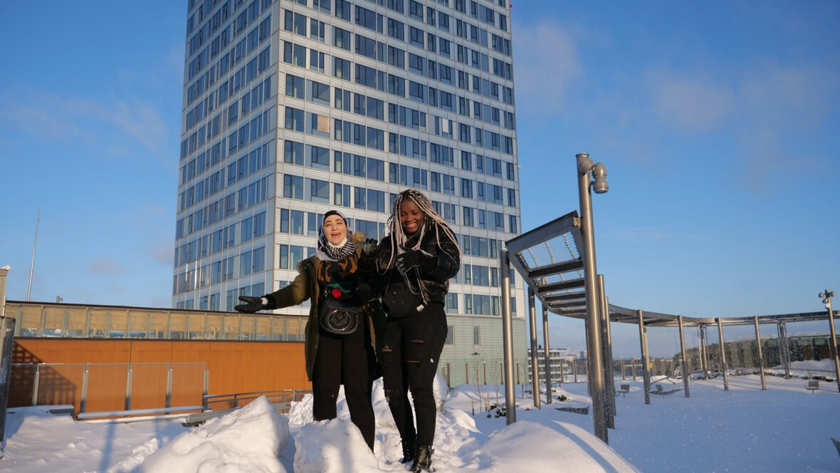 Kaksi nuorta seisoo lumihangessa auringon paistaessa, taustalla korkea kerrostalo.