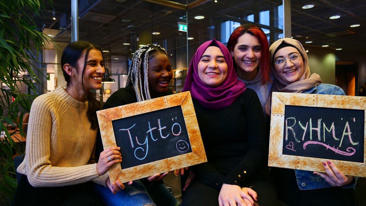"""Viisi nuorta hymyilee iloisina ryhmäkuvassa. Heillä käsissään kyltit joissa lukee """"Tyttöryhmä"""""""