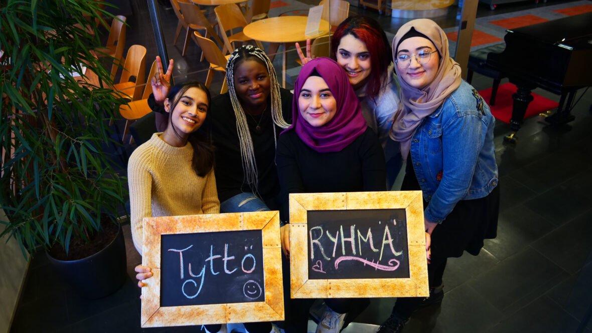 """Joukko nuoria poseeraa kameralle. Heillä käsissään kyltit joissa lukee """"Tyttöryhmä""""."""