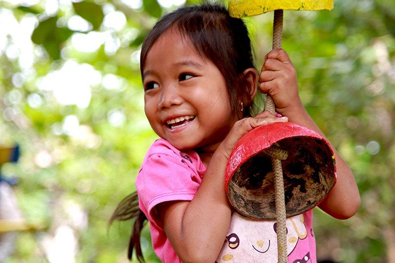 Kambodzalainen tyttö leikkii ulkona.