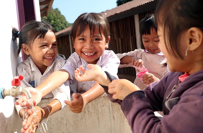 Laosilaisia lapsia pesemässä käsiään.