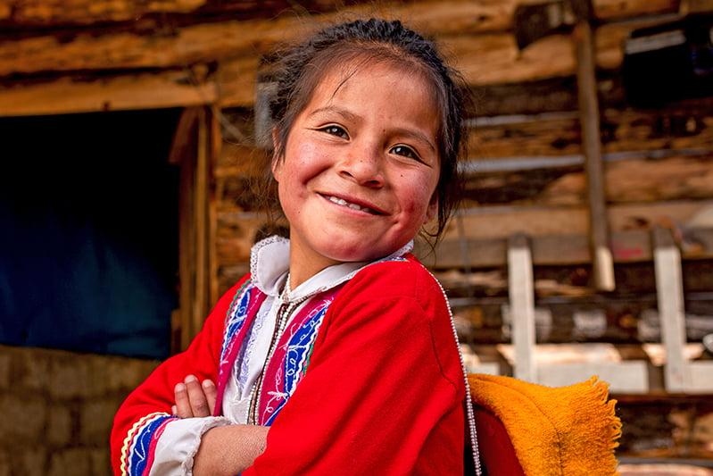 Perulainen tyttö hymyilee kameralle puisen seinän edessä.