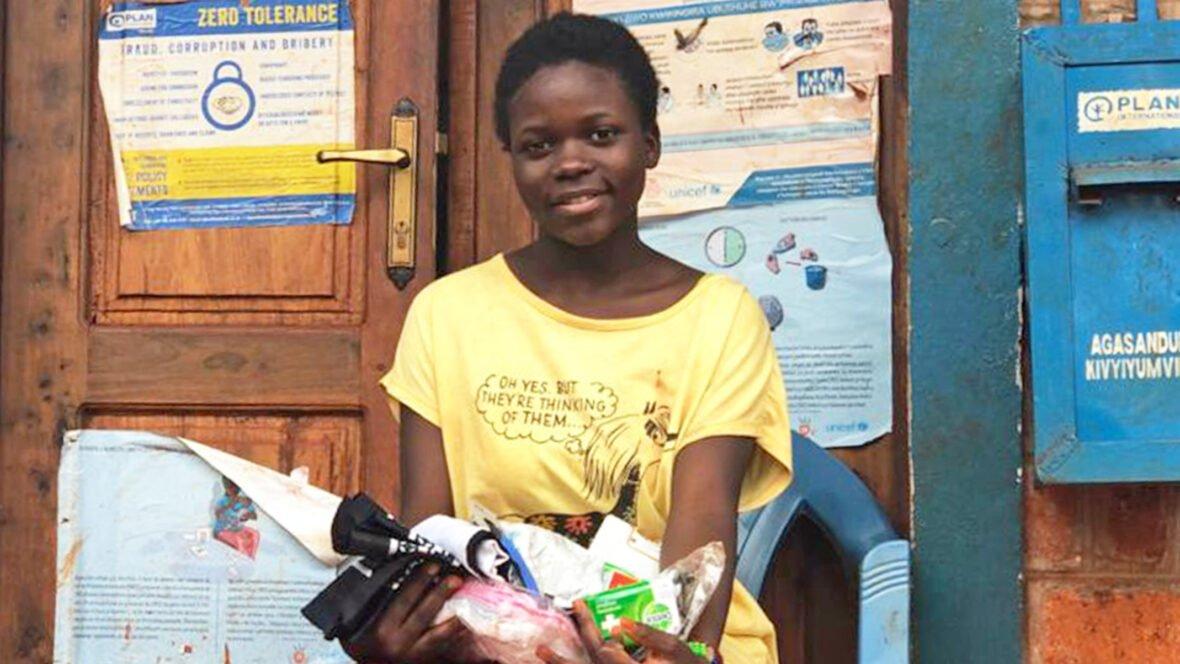 14-vuotias burundilaistyttö Angel istuu Tansaniassa tuolilla, sylissään kuukautishygieniatarvikkeita.