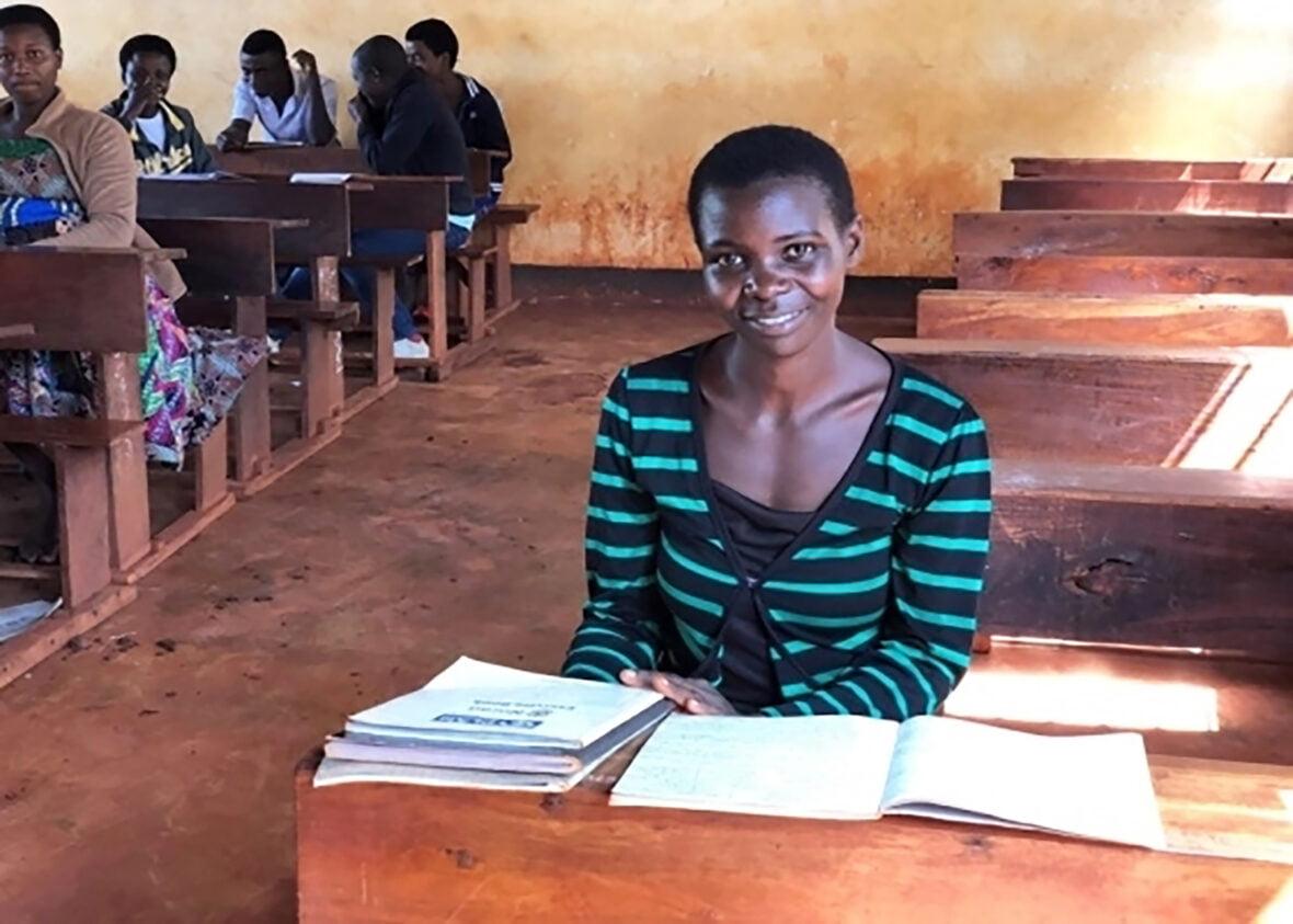 23-vuotias burundilainen Citigestse istuu pulpetissa koulussa Tansaniassa.