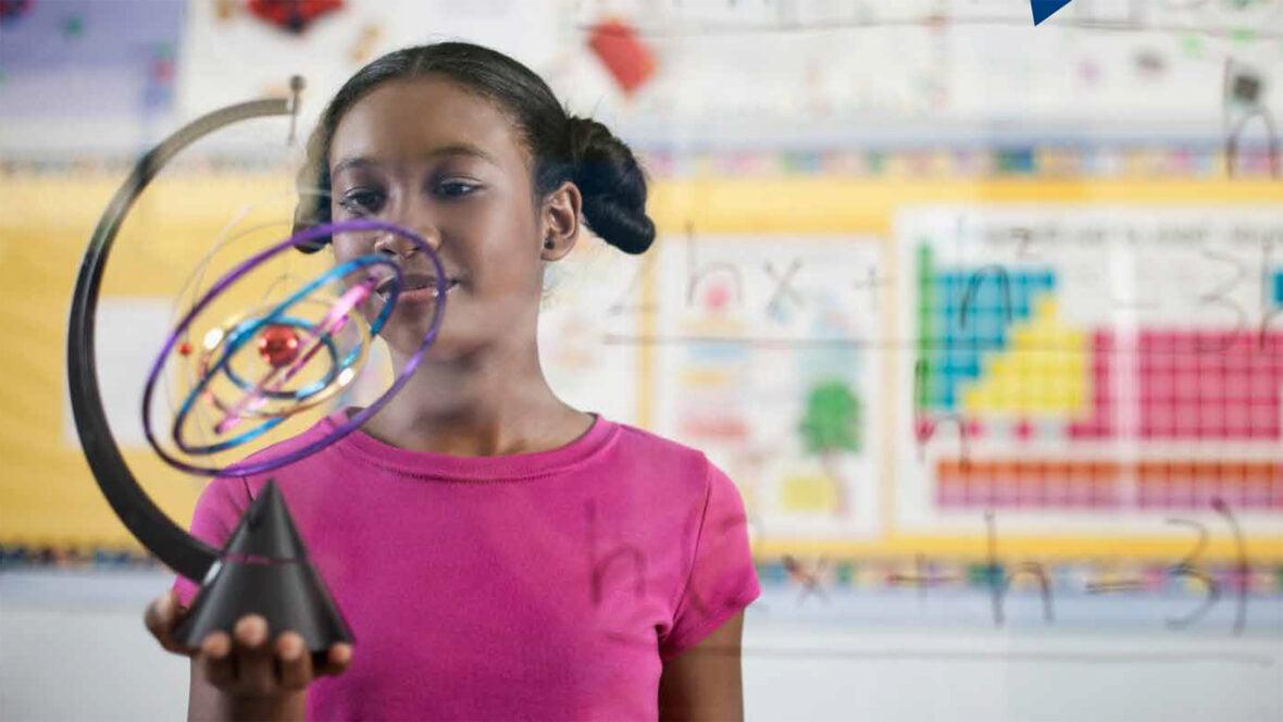 Pinkkipaitainen tyttö pitää kädessään aurinkokuntaa ja planeettojen kiertoratoja kuvaavaa laitetta.