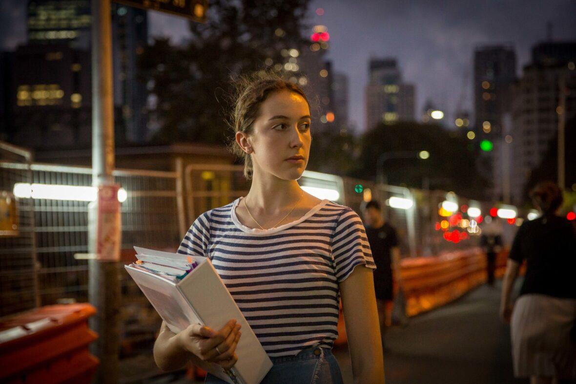 Tyttö kansio kädessä suurkaupungin kadulla illalla.
