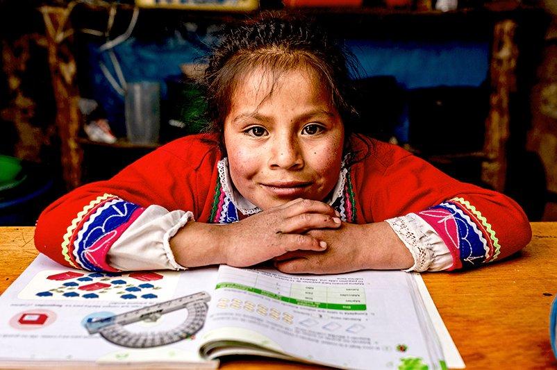 Tyttö istuu pöydän ääressä koulukirja edessään.