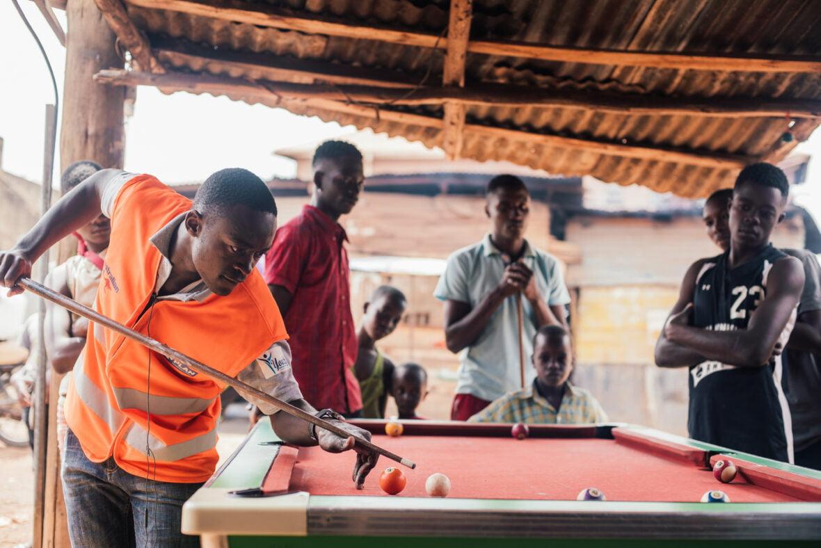 Ugandalaisnuoret pelaavat biljardia.
