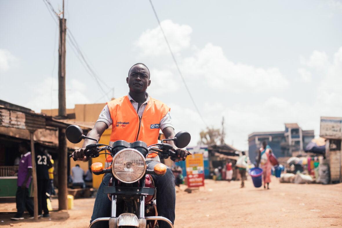 Ugandalaisnuori ajaa mopolla Kampalassa.