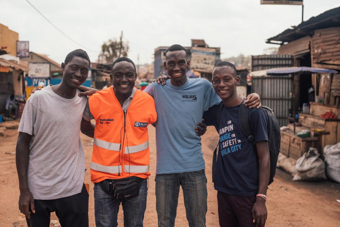 Ugandalaisnuoret poseeraavat yhdessä Kampalan kadulla.
