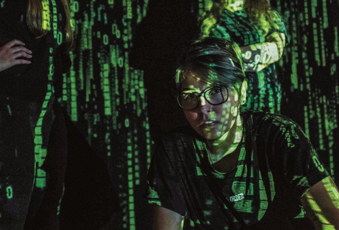 Nuori, johon on heijastettu projektorilla mustavihreää digitalista kuvaa.
