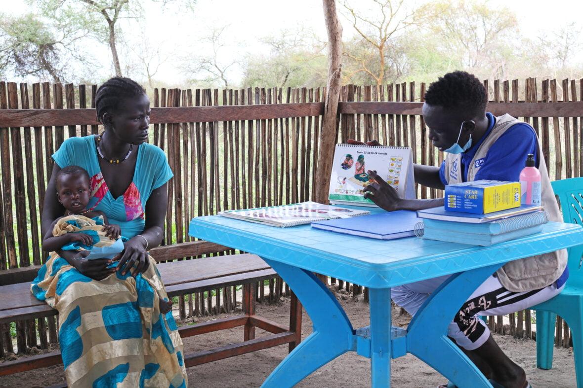 18-vuotias etiopialaisnainen vauvansa kanssa terveydenhoitajan puheilla terveysklinikalla Etelä-Sudanissa.