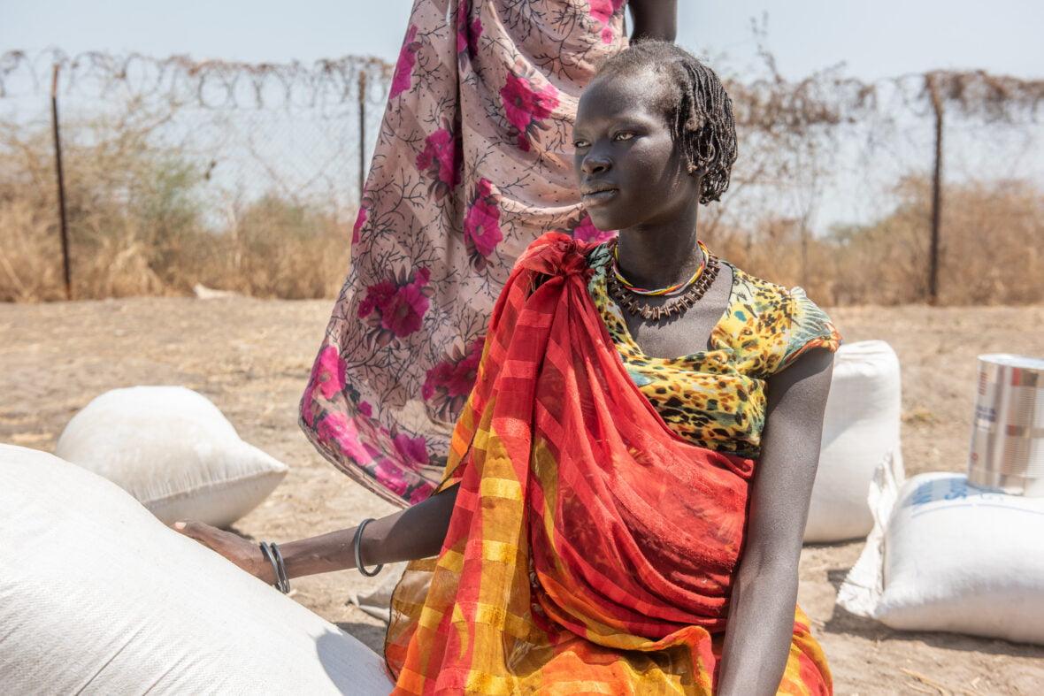 Eteläsudanilainen Adengin istuu keskellä ruokasäkkejä ja kuivaa maaperää.