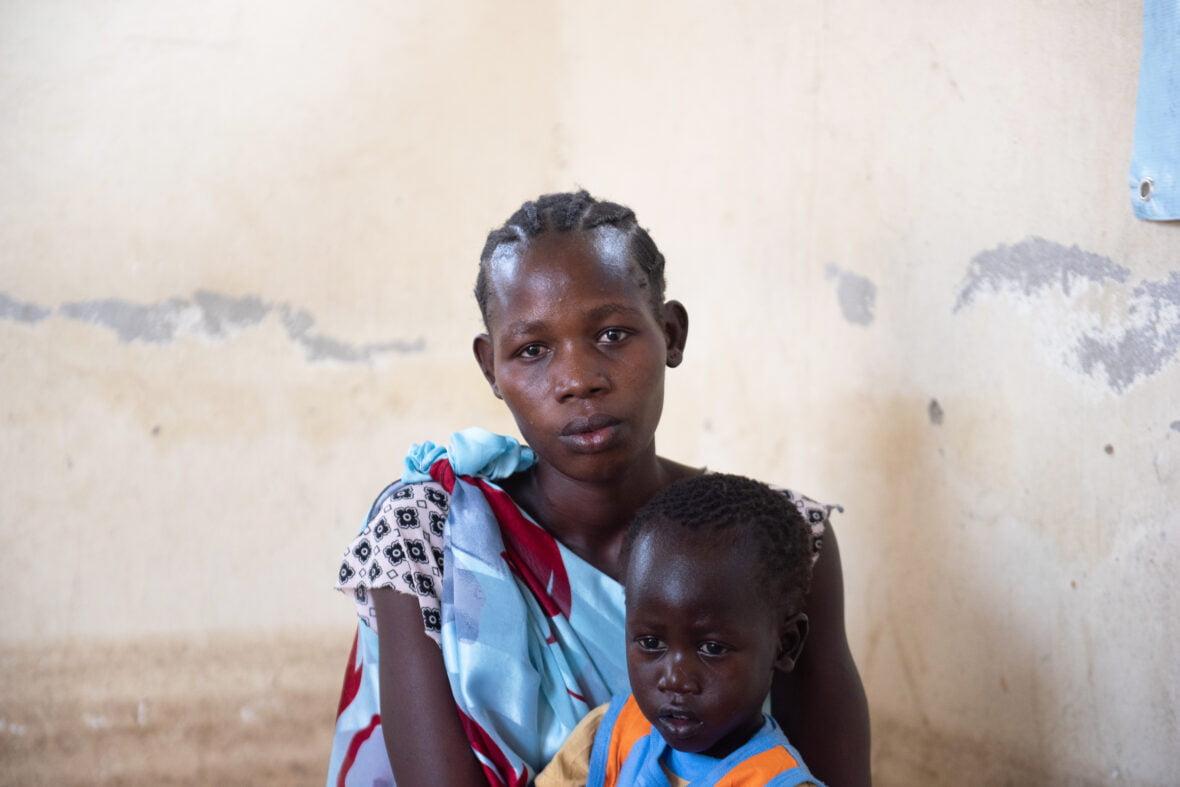 Äiti ja kolmevuotias lapsi istuvat huoneessa Etelä-Sudanissa.