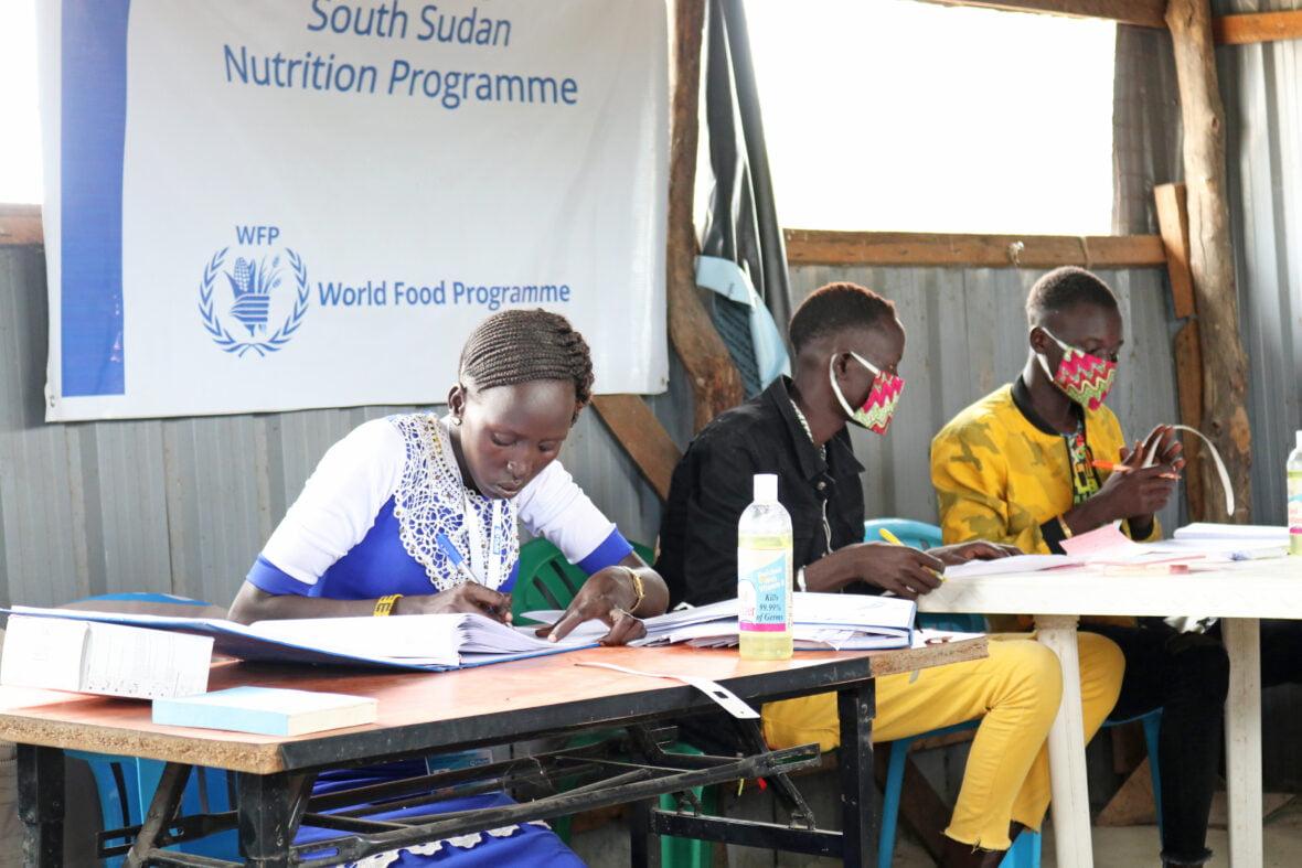 Avustustyöntekijät työskentelemässä pöydän ääressä Etelä-Sudanissa.