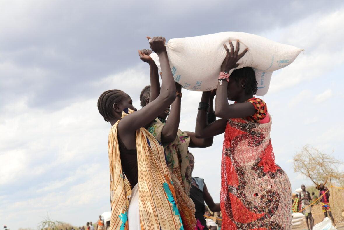 Eteläsudanilaiset naiset kantavat ruokasäkkiä.