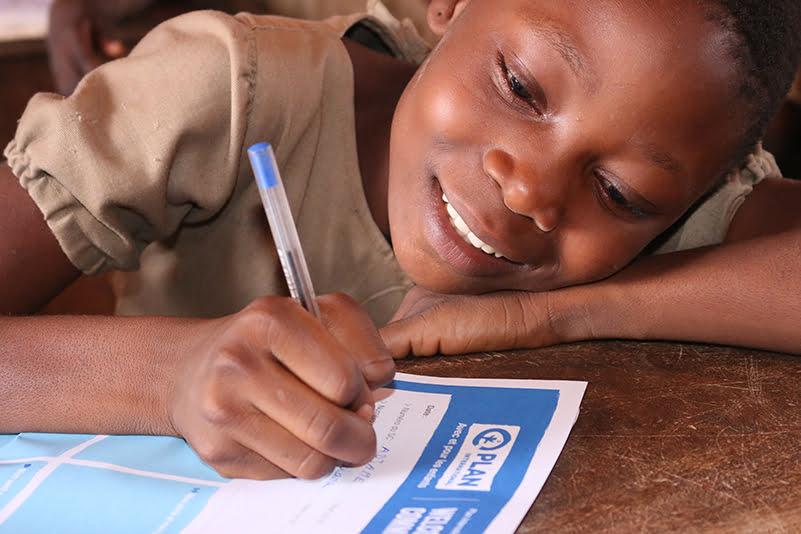 Beniniläinen kummilapsi kirjoittaa kirjettä pöydän ääressä.