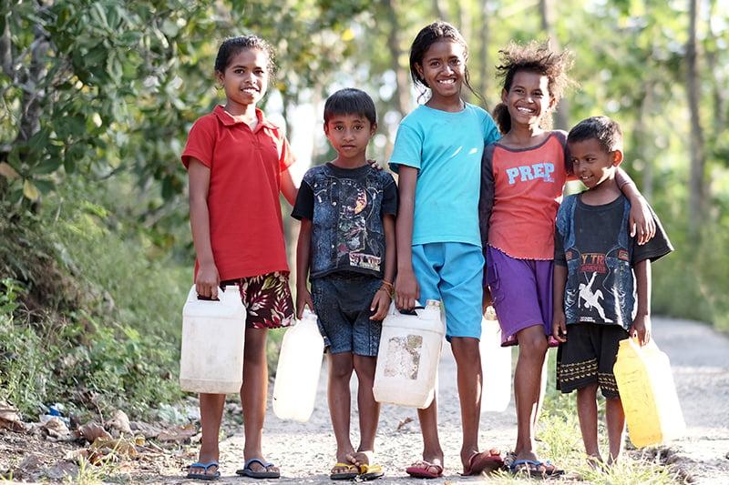 Indonesialaisia lapsia seisoo tiellä hymyillen.