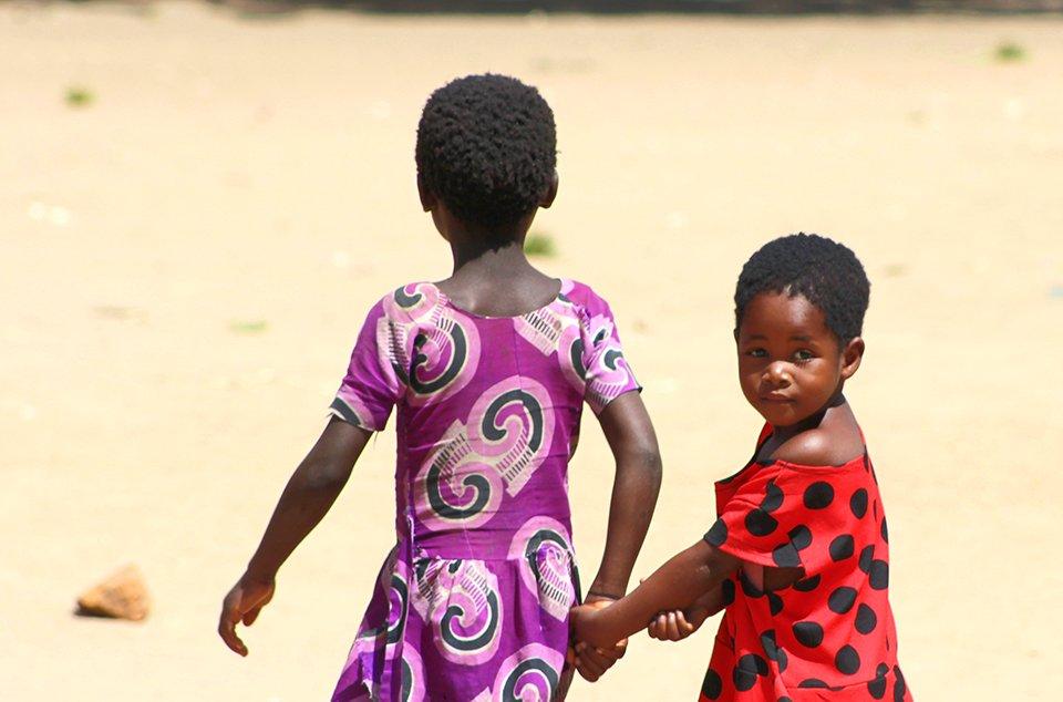 Kaksi tyttöä kävelee käsikkäin pois kamerasta ja toinen kurkistaa olkansa yli kohti kameraa.