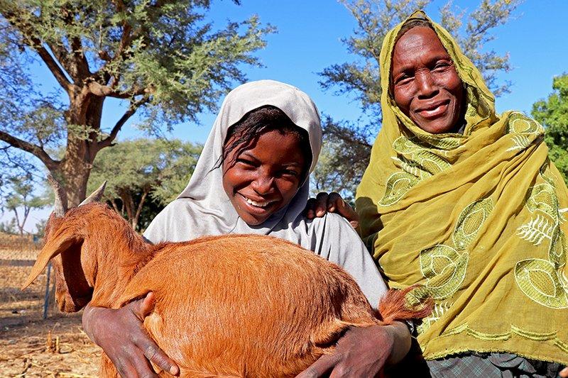 Äiti ja tytär hymyilevät kameralle. Tyttärellä on sylissään vuohi.