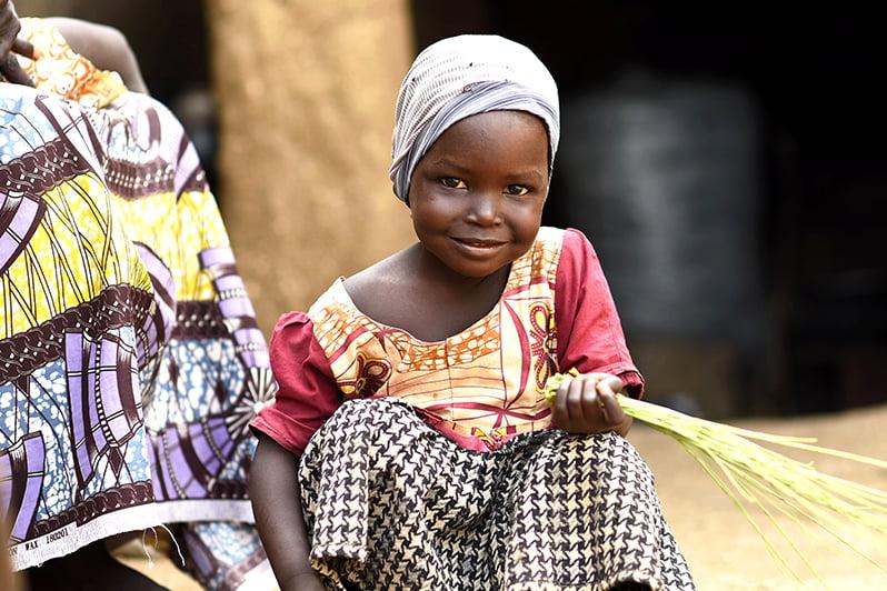 Nigerialainen tyttö on kyykistynyt ja pitelee kädessään ruokoja.