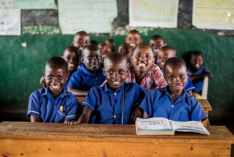 Ryhmä ruandalaisia lapsia istuu koululuokassa sinisissä koulupuvuissa ja katsoo hymyillen kohti kameraa.