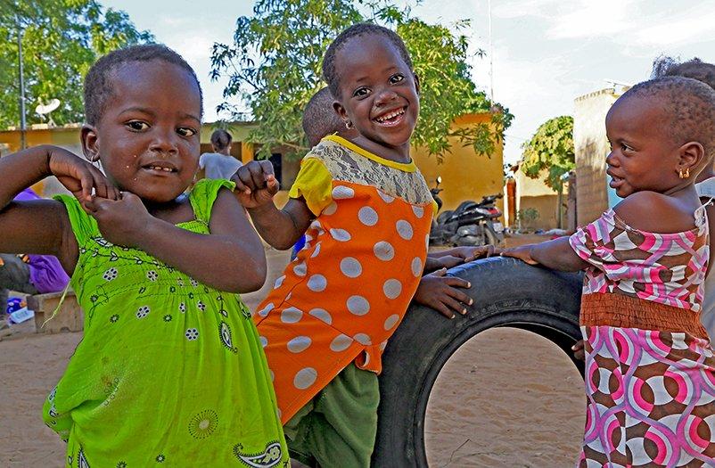 Senegalilaisia pikkulapsia leikkimässä ulkona.