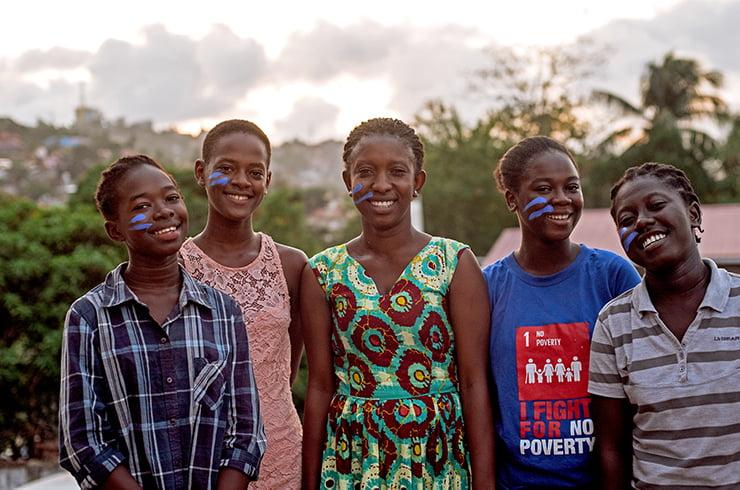 Ryhmä sierraleonelaisia nuoria poseeraa kameralle maiseman edessä.