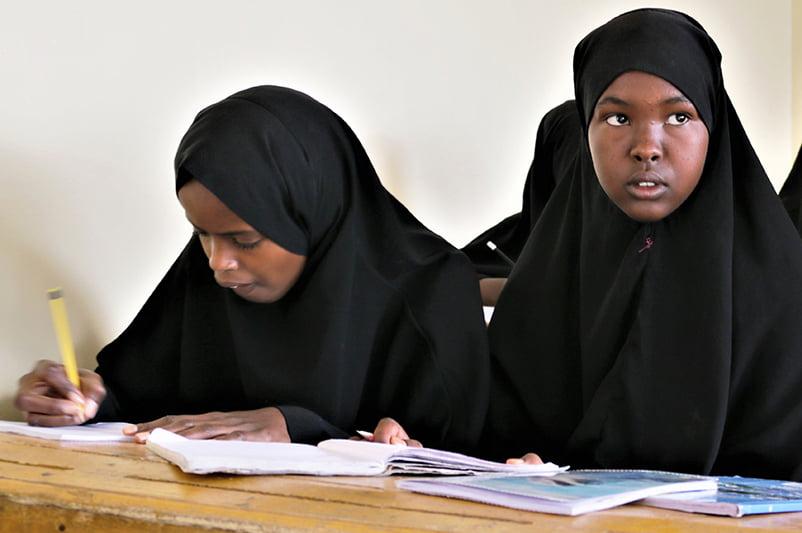 Kaksi somalialaista tyttöä tekee tehtäviä pulpetin ääressä.